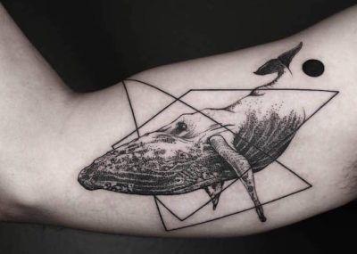 черное тату кита на бицепсе