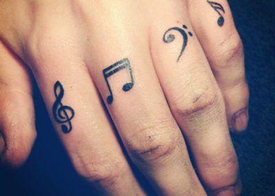 Тату на пальцах ноты и скрипичный ключ